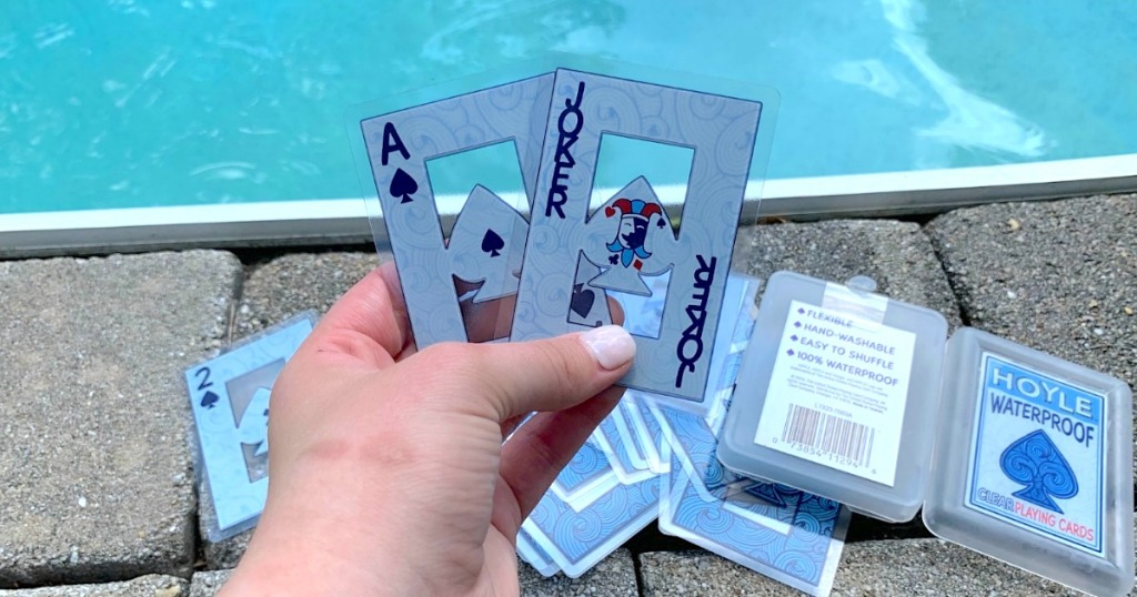 holding waterproof playing cards with pool in the background