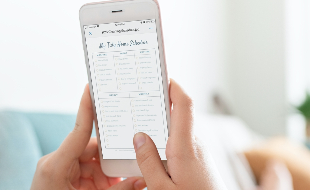 hands holding a phone with cleaning schedule on screen