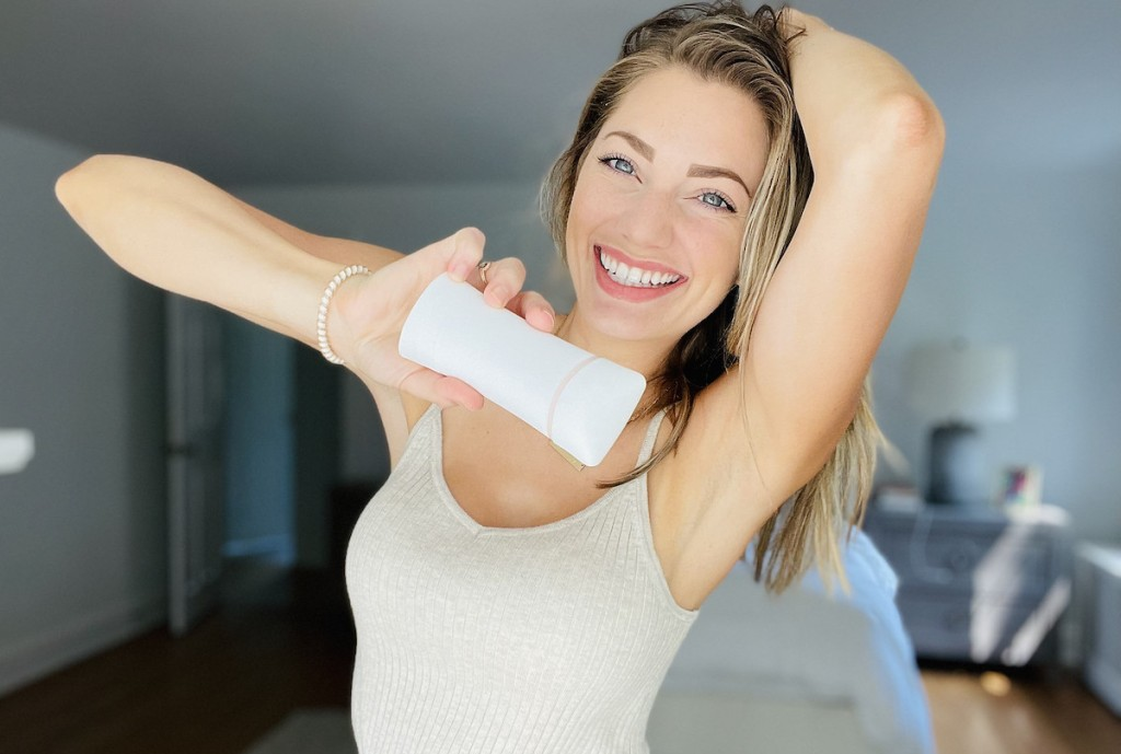 woman holding up stick of deodorant with arms over head smiling