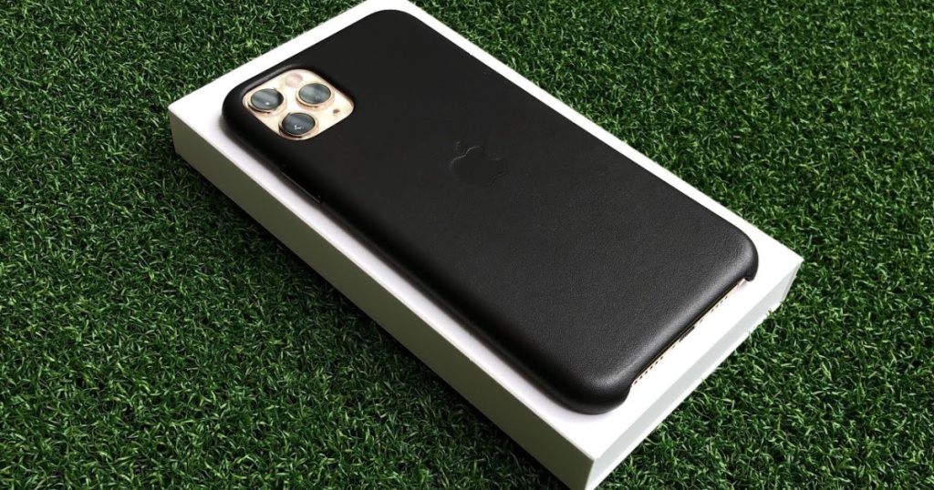 iPhone with black case sitting on white product box on green turf