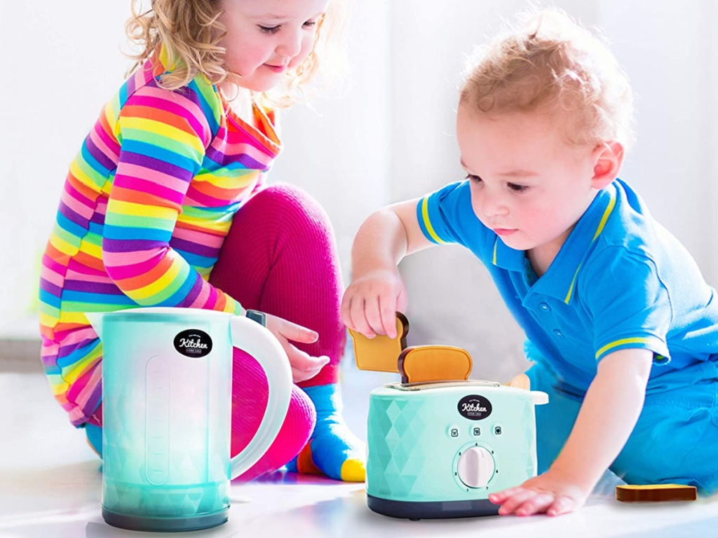 boy and girl playing with toy toasted and kettle