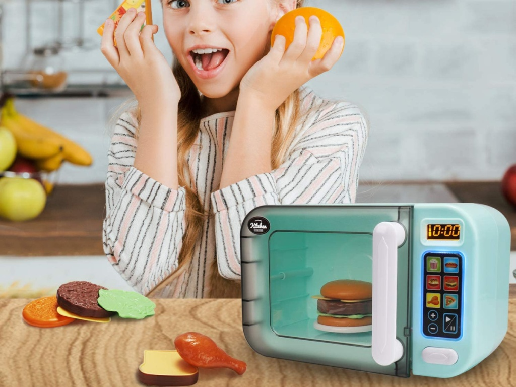 girl playing with toy microwave and food