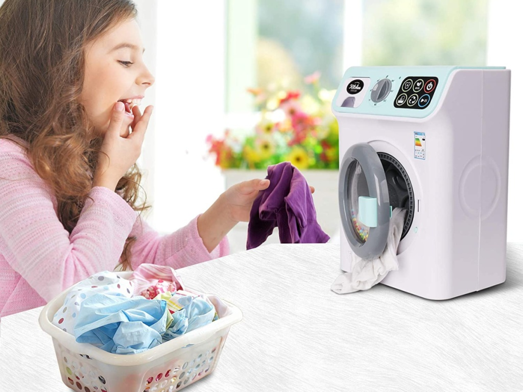 girl playing with toy washing machine and small basket of laundry