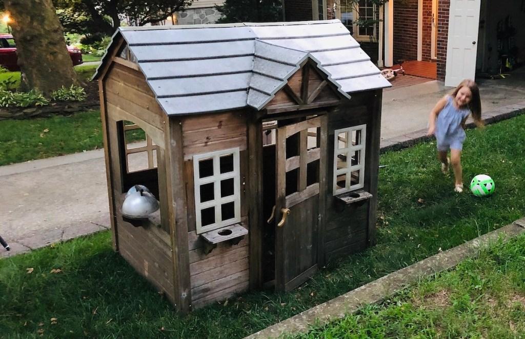 dirty kids playhouse sitting in yard on grass
