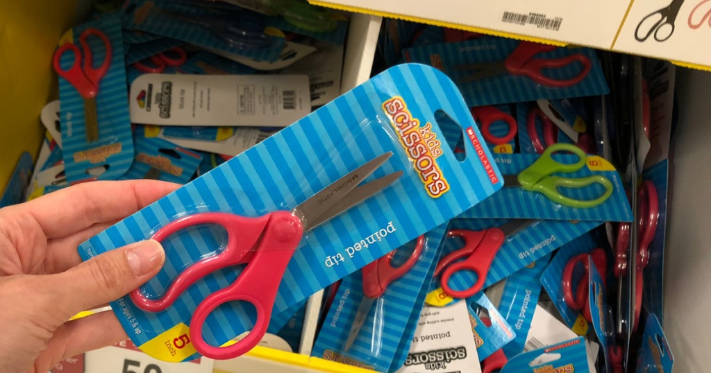 hand holding red colored kids scissors in store