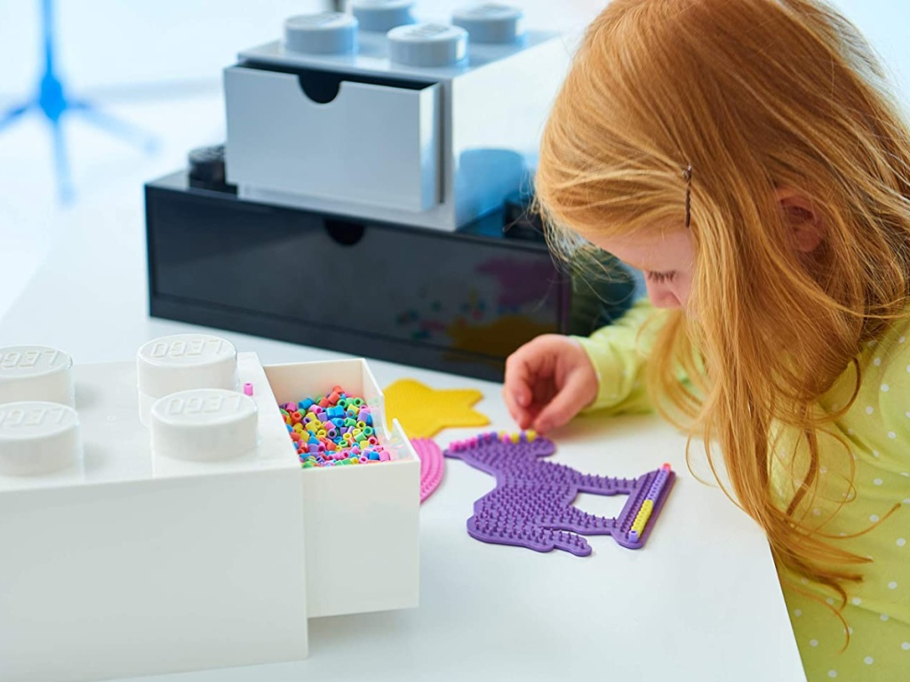 little girl making crafts at table