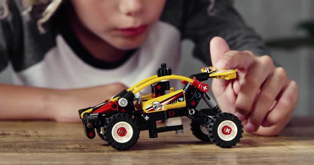 boy playing with a red, yellow, and black lego dune buggy
