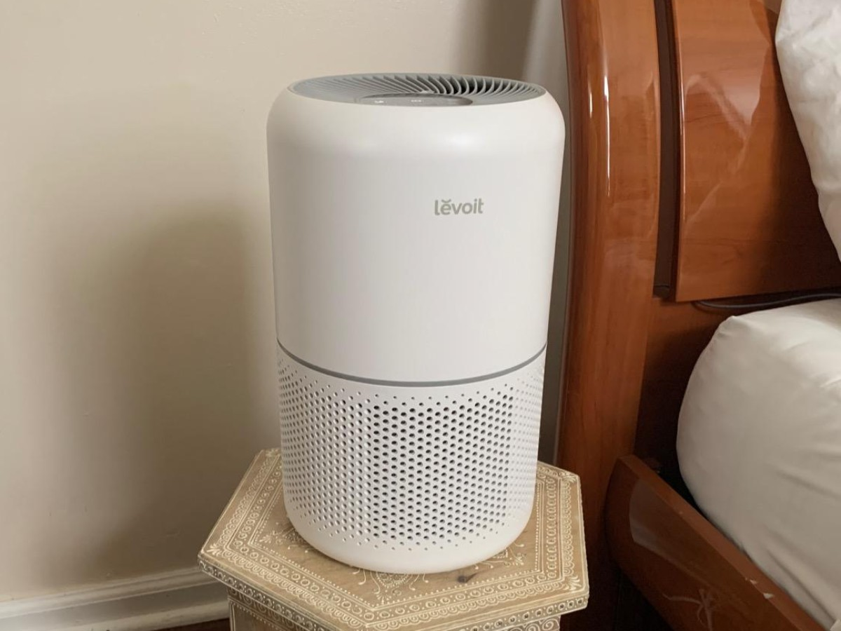 white levoit air purifier sitting on side table next to bed