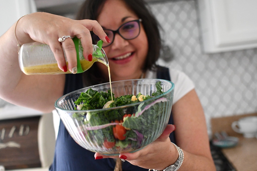 Lina pouring dressing into salad