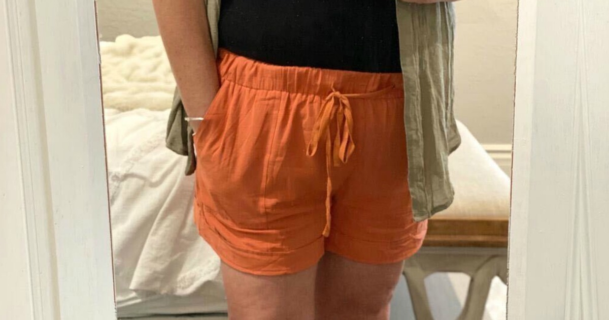 woman wearing a pair of orange shorts and black shirt standing in front of a mirror