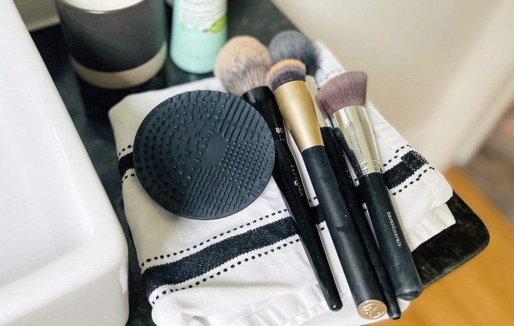 makeup brushes and black silicone mat laying on stripe towel in bathroom