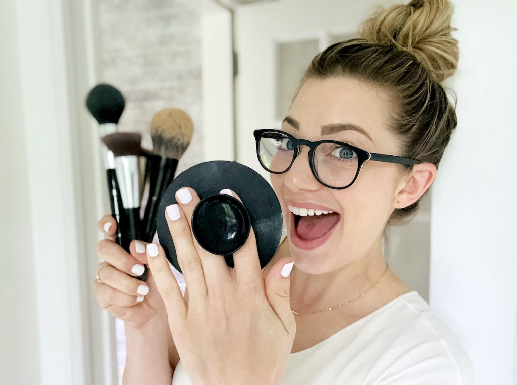 woman holding pop socket silicone mat and makeup brushes