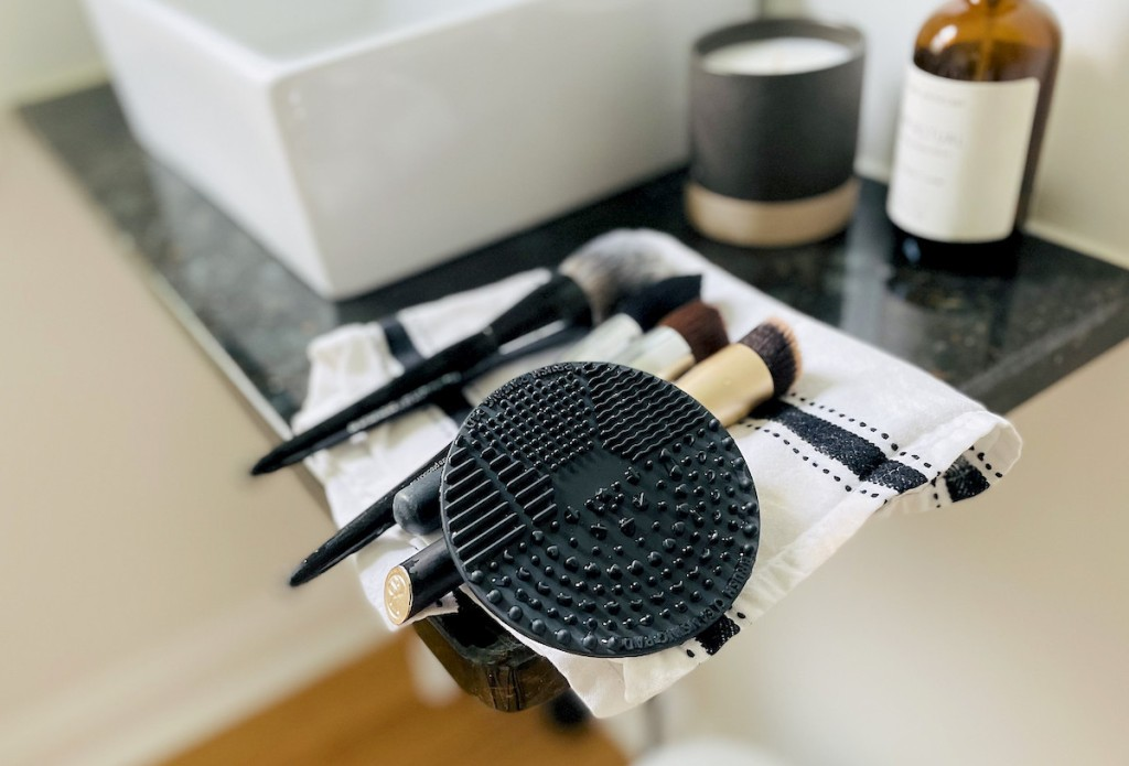 makeup brushes and black silicone mat on stripe towel on bathroom counter