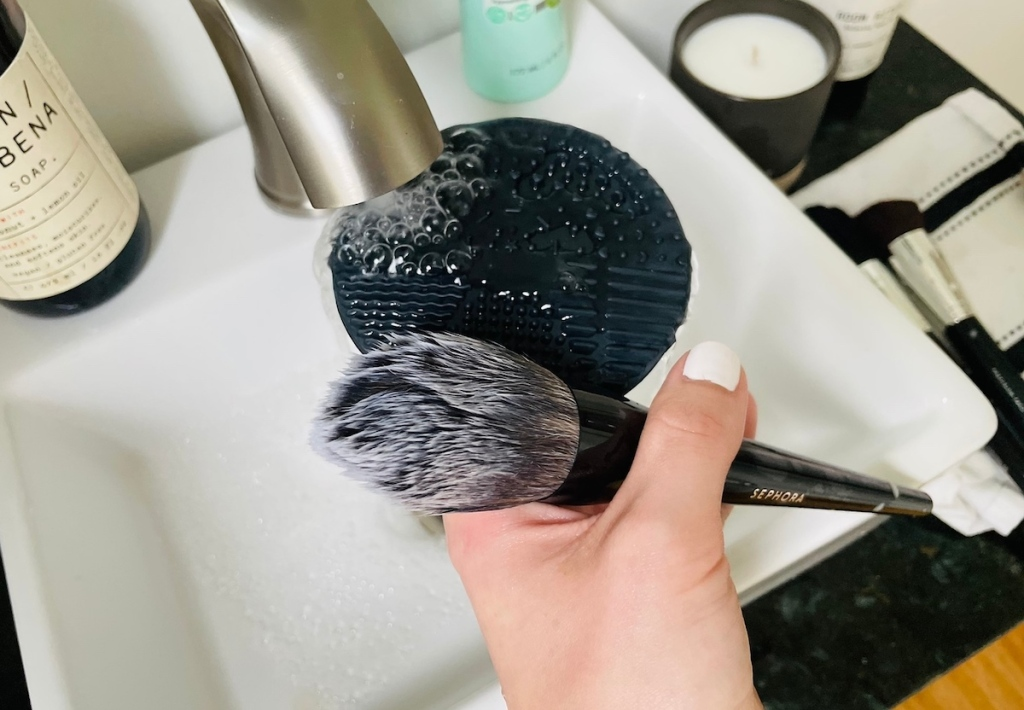 black silicone mat and makeup brush under running faucet in bathroom sink