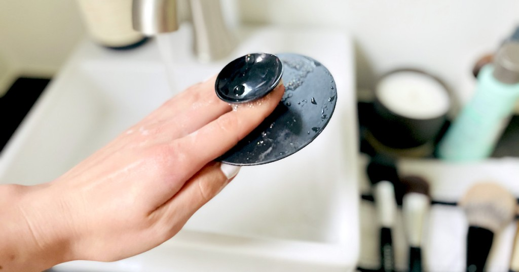 hand holding pop socket on black silicone mat
