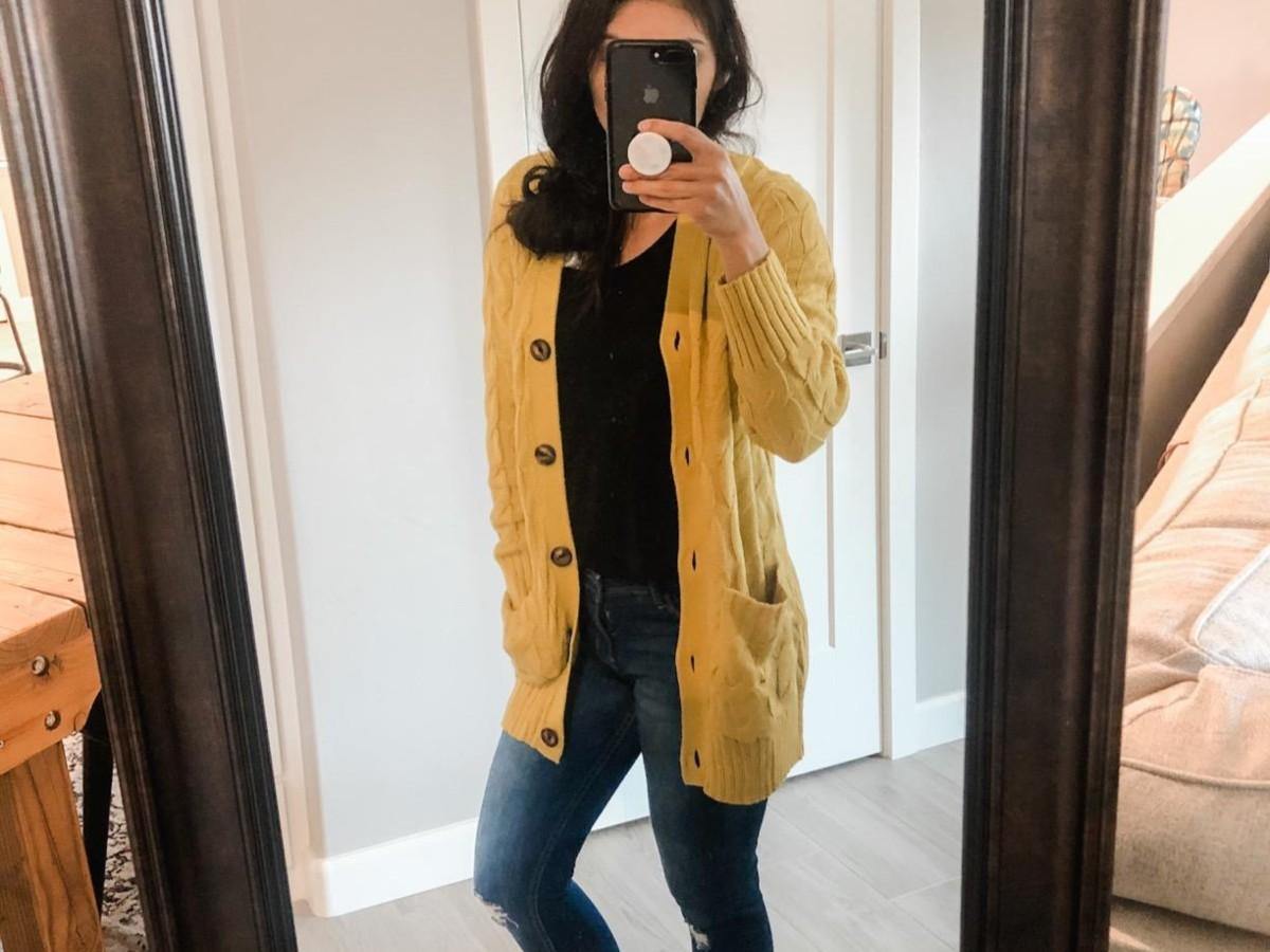 woman taking selfie in yellow cardigan