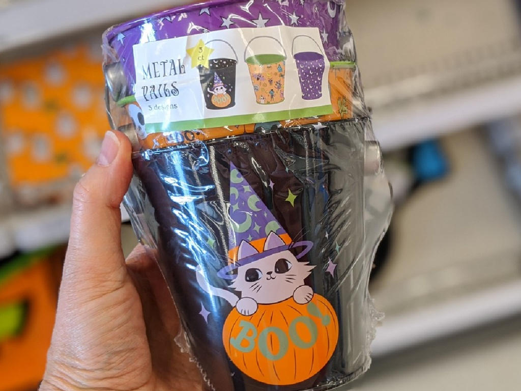 hand holding stack of metal pails with Halloween decor on them
