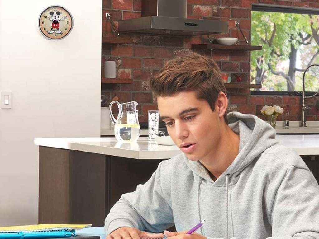 boy studying and Mickey Mouse clock timer hanging on wall