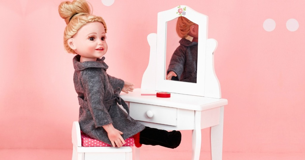 doll seated at a toy vanity with mirror against a pink wall