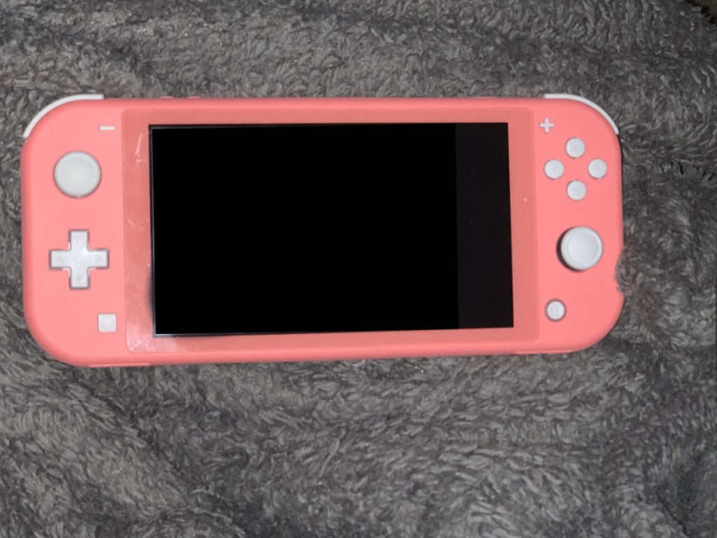coral pink nintendo switch lite on blanket