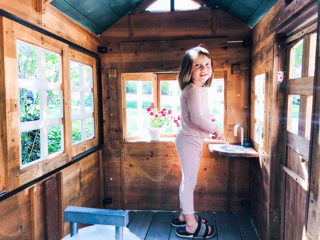 girl standing inside of kids playhouse