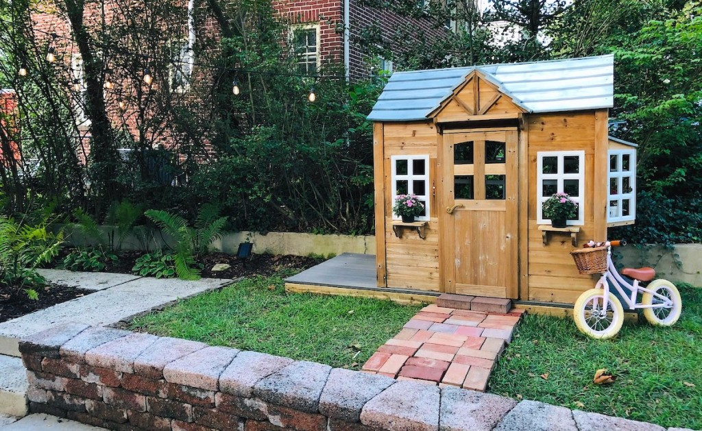 kids playhouse outside in grass with bike