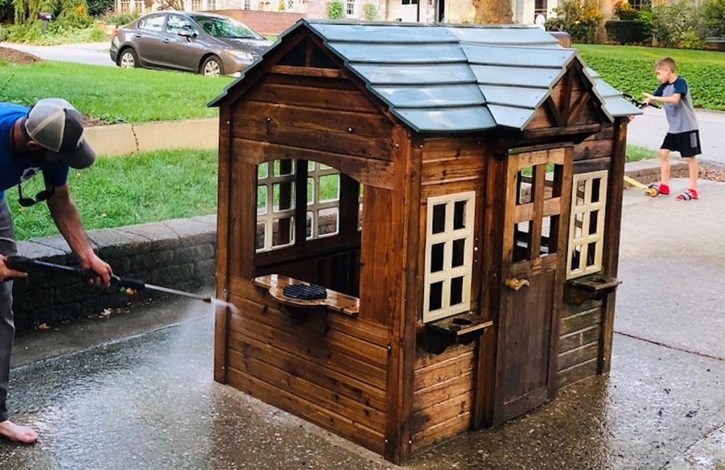 man power washing kids playhouse in driveway