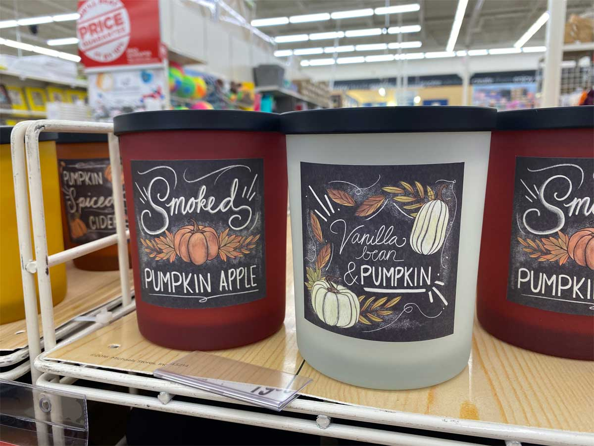 glass jar candles with fall scents on a store display shelf