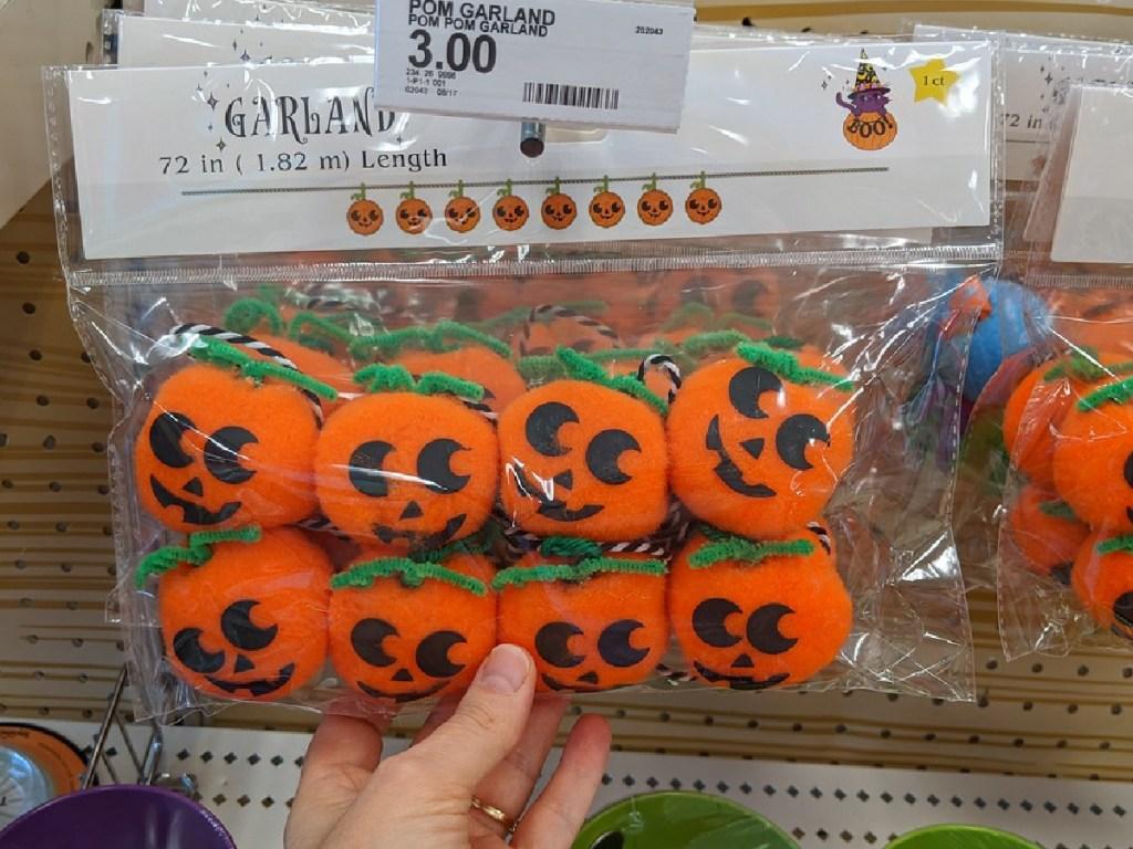 hand holding bag of little plush pumpkins by store shelf