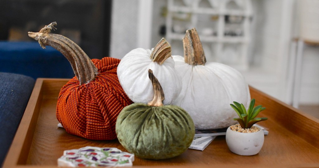pile of various velvet pumpkins sitting on wood tray table