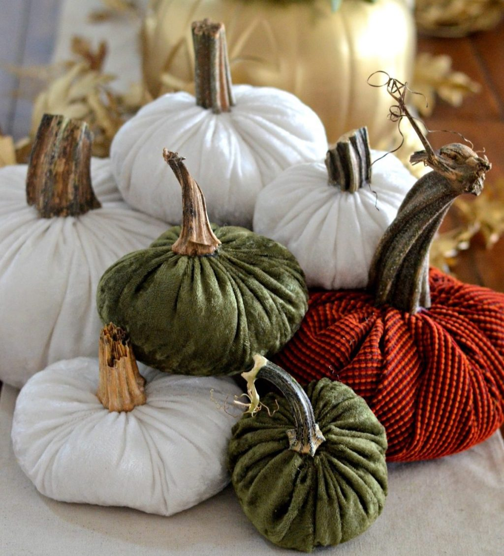pile of velvet pumpkins in a stack on table