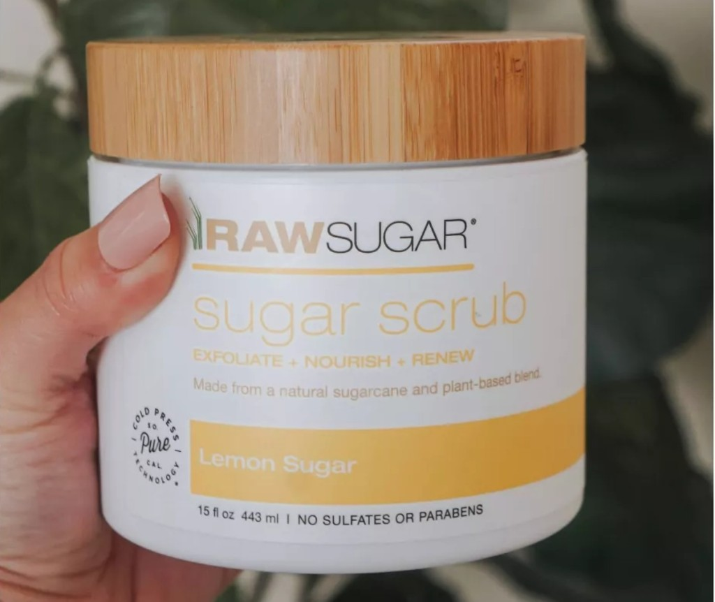 hand holding sugar scrub with bamboo lid