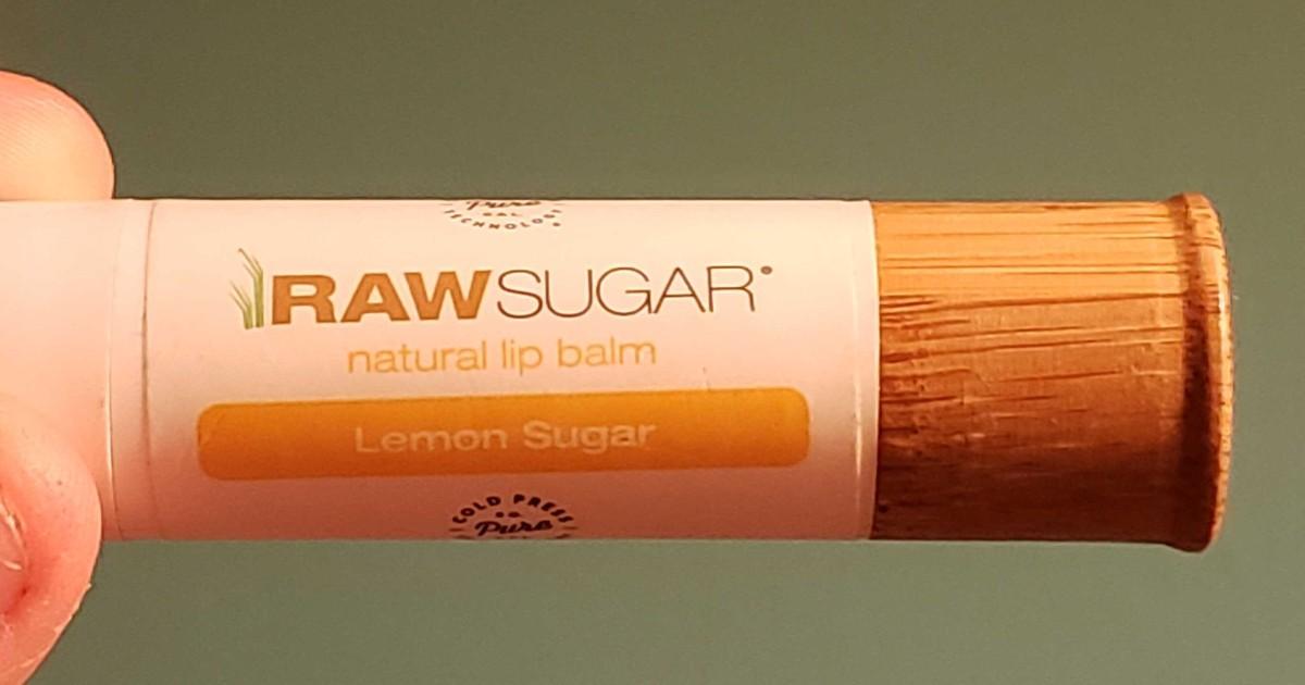hand holding Raw Sugar lip balm