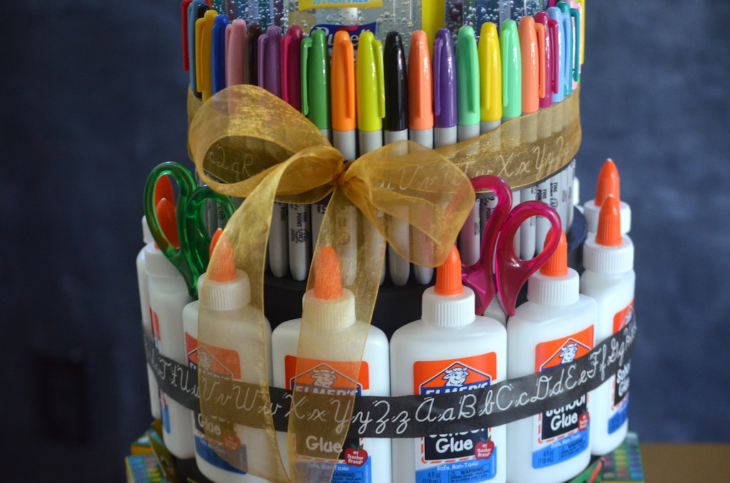 "putting ribbon around school supply ""cake"""