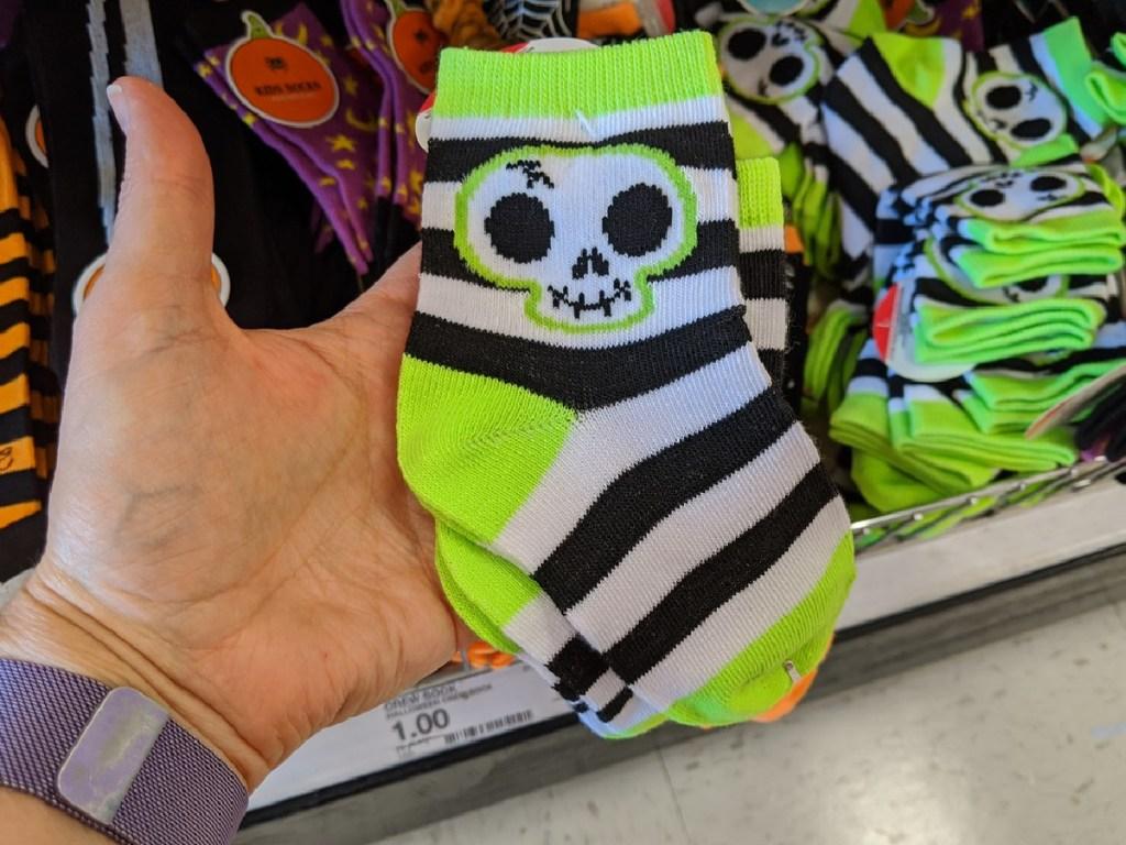 hand holding green & black little kids socks by store shelf