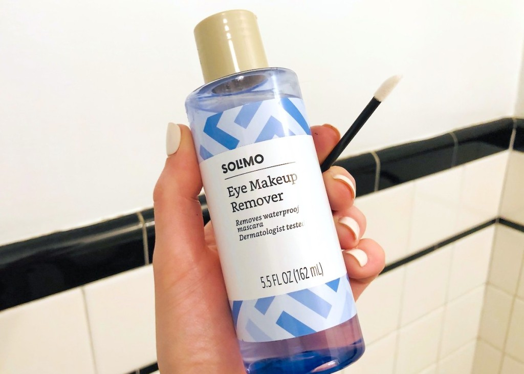 hand holding a blue bottle of makeup remover with cotton swab
