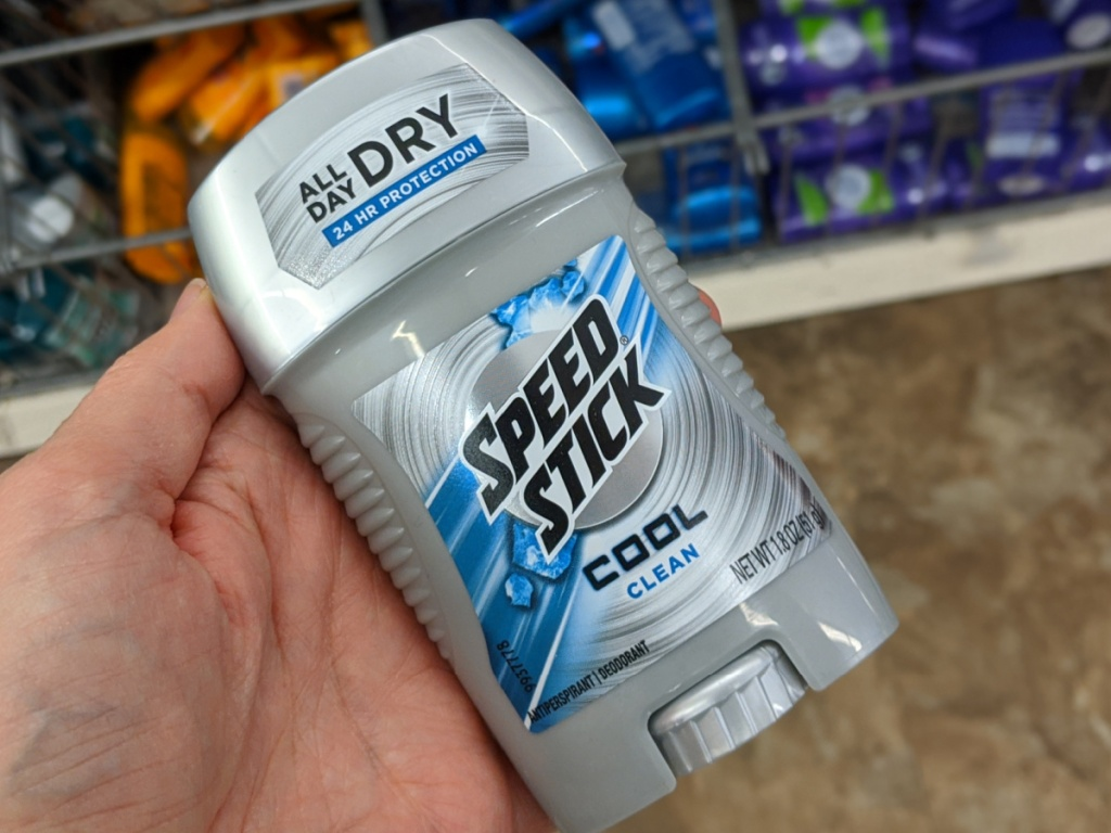 hand holding stick of deodorant by store display