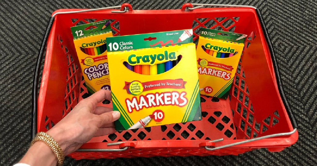 hand holding Crayola Markers in front of basket with other crayola items