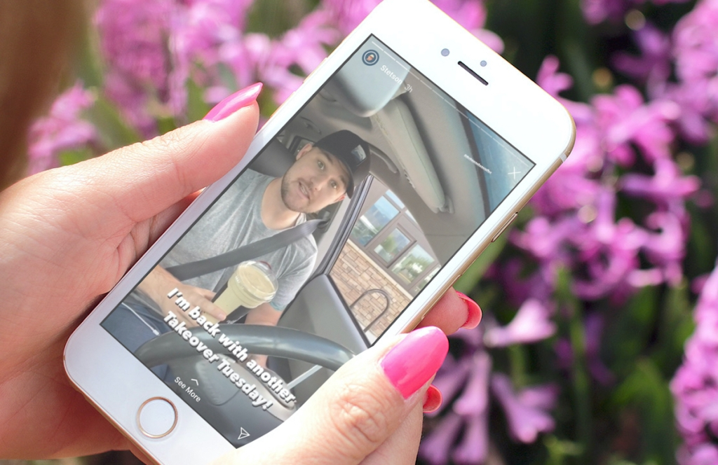 hands holding a cell phone with man on screen