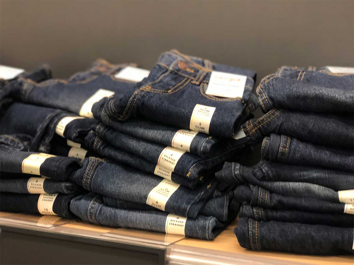 kids jeans stacked up on display in store