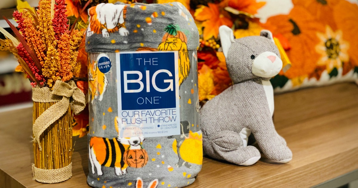 packaged throw blanket next to a stuffed toy dog in front of fall foliage