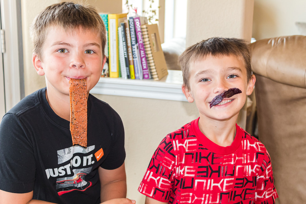 two boys being goofy with fruit rolls up