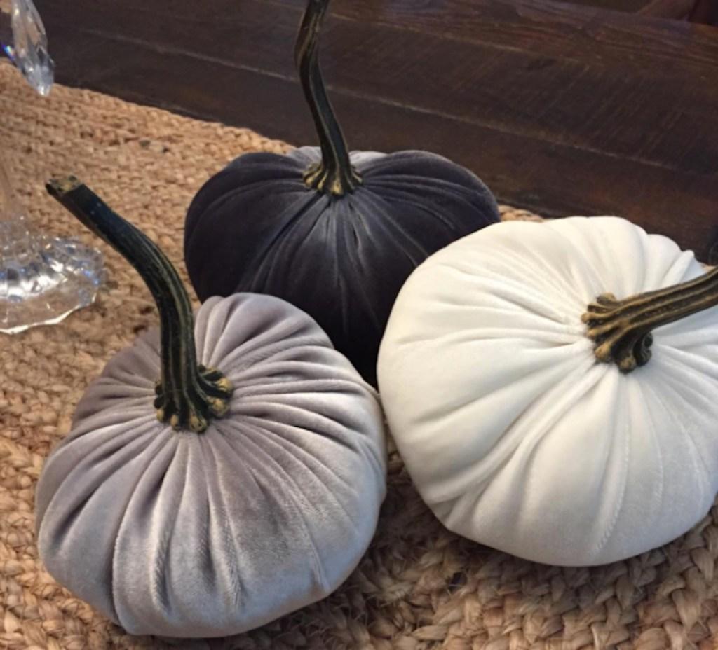 gray and white velvet pumpkins on jute table