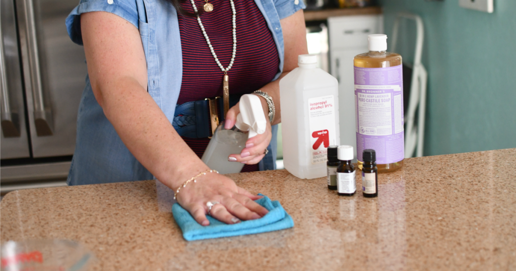 woman cleaning counters with granite spray