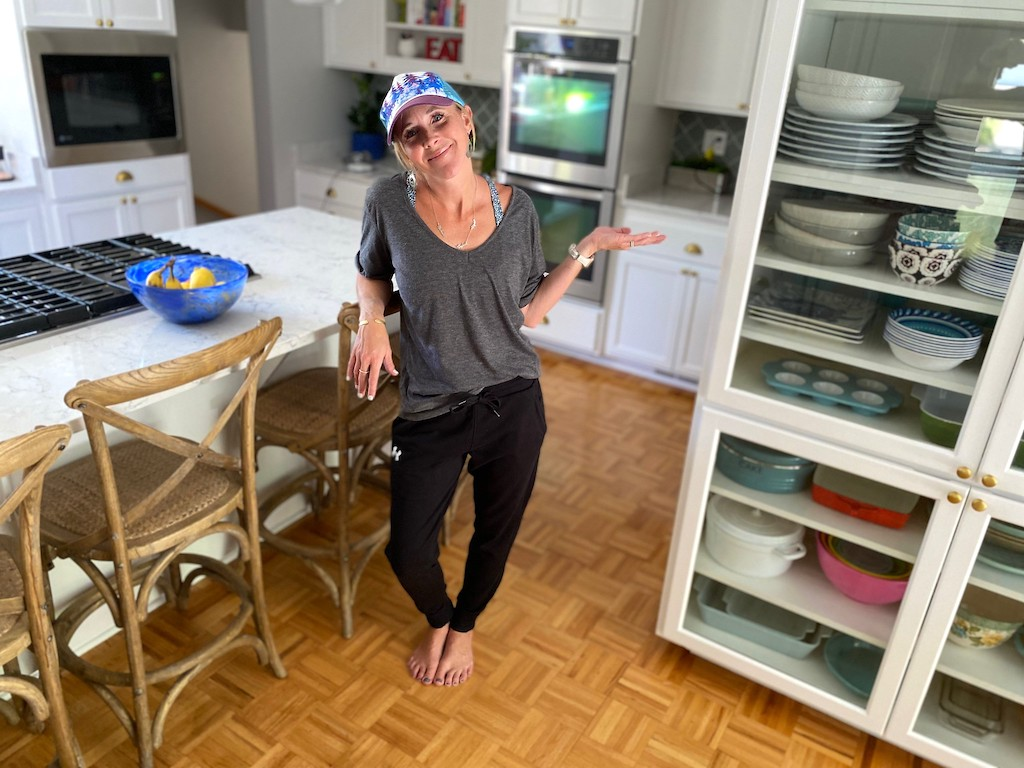 woman wearing UA joggers in kitchen with hat on