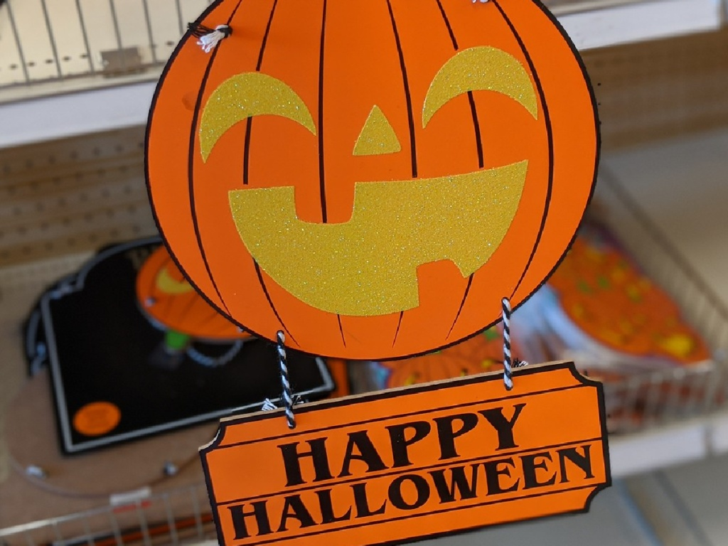 wooden sign shaped like pumpkin by store display
