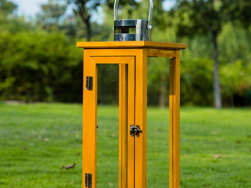 wooden lantern top sitting in the grass near trees