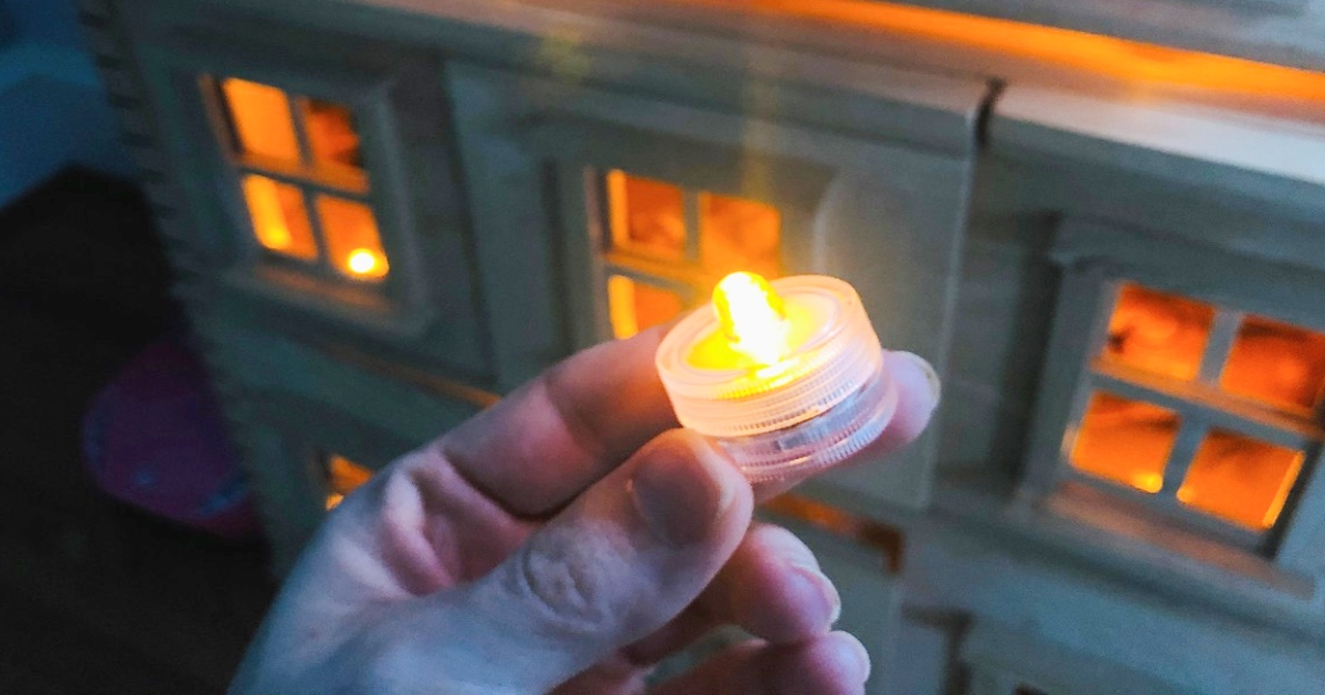 a hand holding a yellow tea light, in front of a dollhouse lit up with tea lights