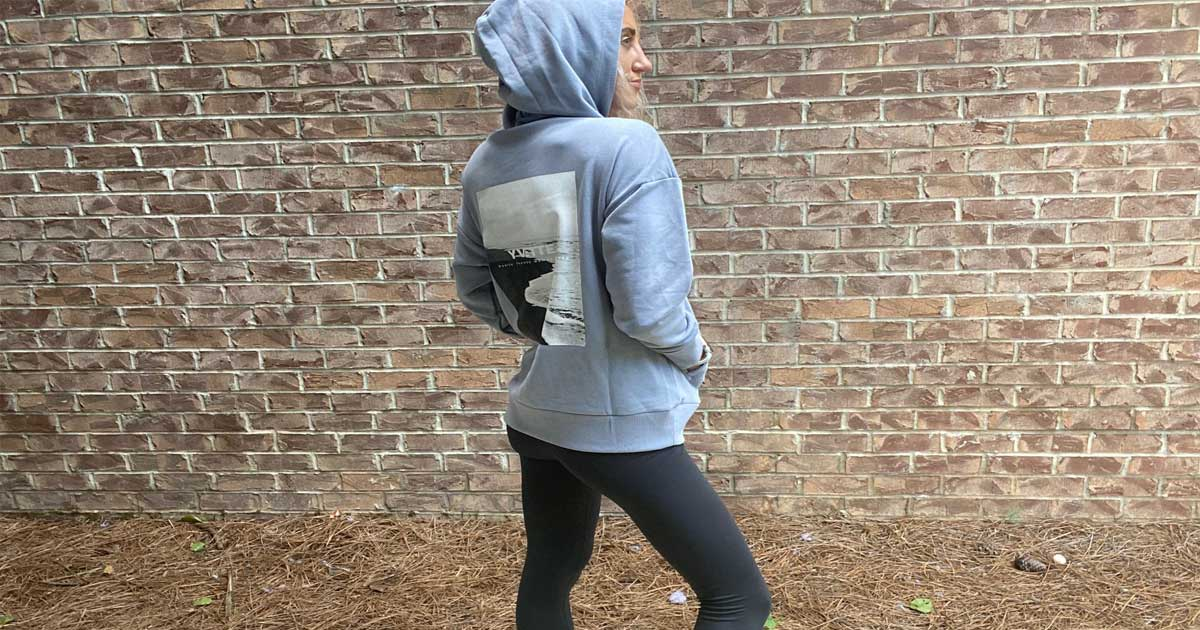 woman wearing a hoodie and leggings standing in front of brick wall