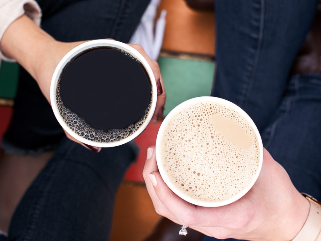two hands holding cups of coffee